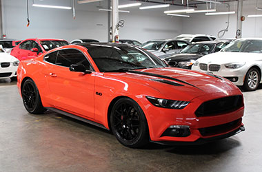 Red-Orange Ford Mustang sold with used car financing by preowned auto dealership in Hayward, California.