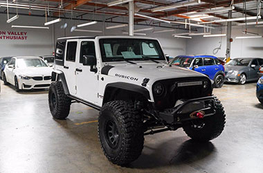 Menlo Park used car dealer with a white Jeep Rubicon for sale.