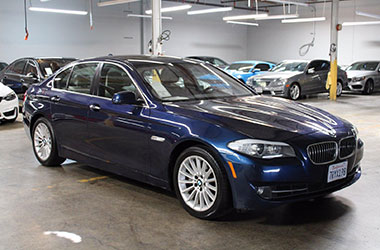 Redwood City preowned dealership with a blue BMW for sale.